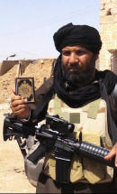 IS fighter holding up a Quran while cradling an assault rifle